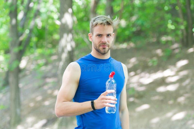 Tomando a ruptura homem na água da bebida do sportswear bebida de refrescamento da vitamina após o exercício Homem atl?tico com g foto de stock