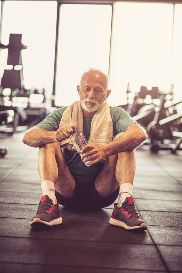Tomando a ruptura Homem no gym imagem de stock