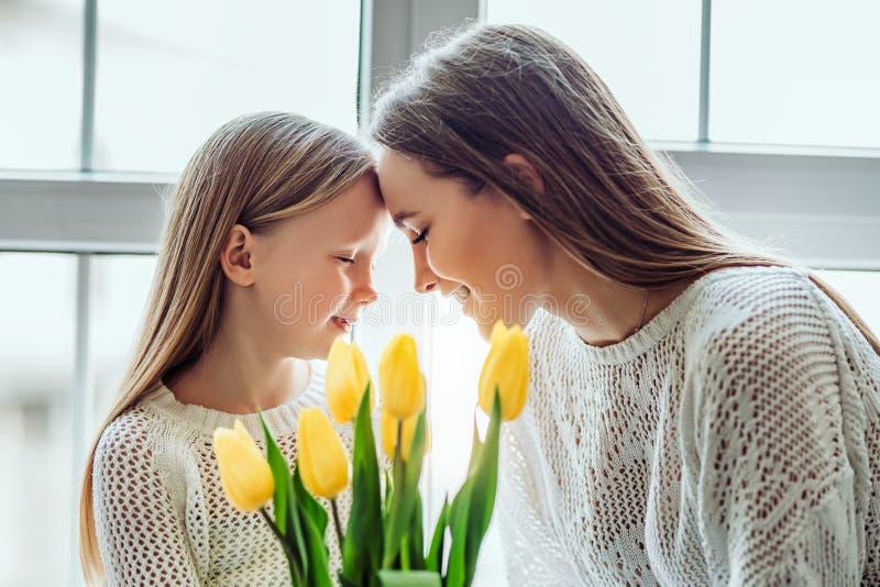 Tomaré siempre el cuidado de usted Madre joven y su hija que ponen sus cabezas juntas mientras que mantiene sus ojos cerrados fotos de archivo