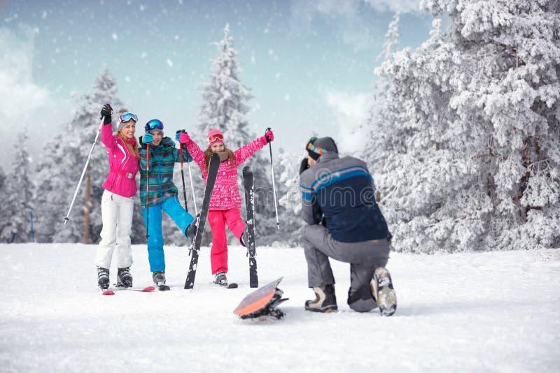 Tomar la fotografía de la familia el vacaciones del invierno en mounta de la nieve imagen de archivo