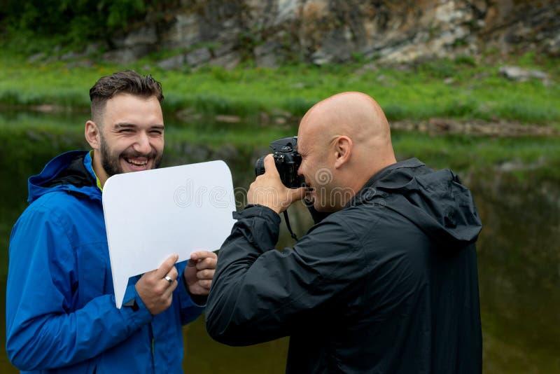 Tomar una imagen o una sesión fotográfica en el aire abierto el fotógrafo está trabajando y el modelo está presentando imagen de archivo libre de regalías