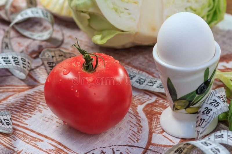 Tomat, ägg, kål och linjal på tabellen arkivfoton