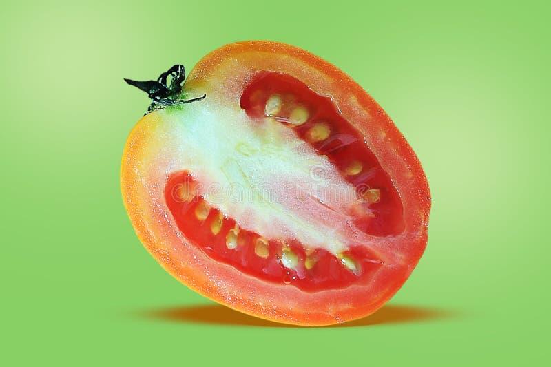 Tomat en halva av tomaten, skivatomat, flyger tomaten som isoleras på gräsplan arkivbilder