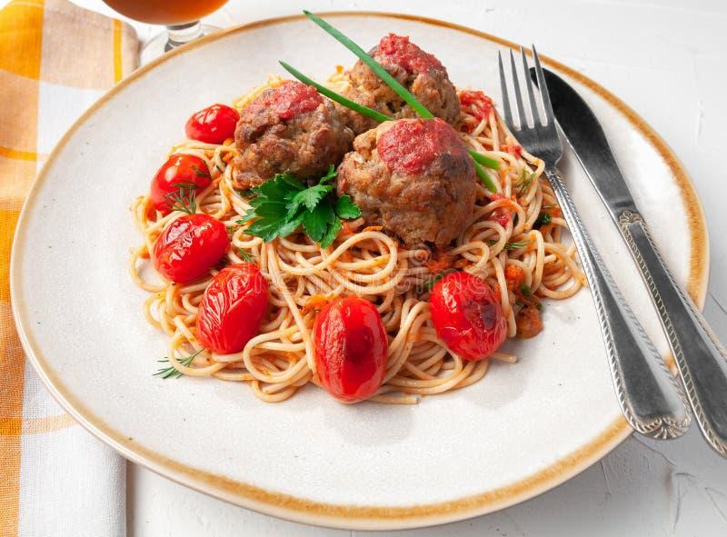 tomat f?r meatballspastas?s Dekorerat med gräsplaner och grillade körsbärsröda tomater I den original- plattan med bestick Besk?d royaltyfri fotografi