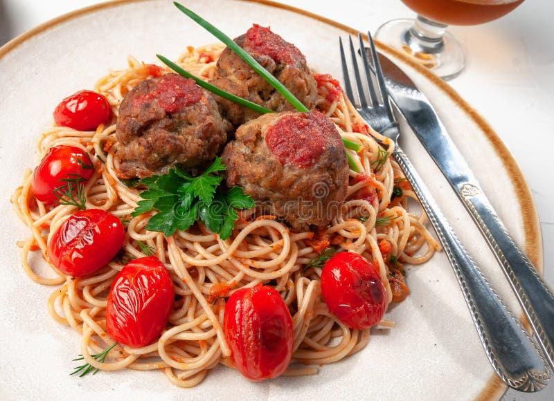 tomat f?r meatballspastas?s Dekorerat med gräsplaner och grillade körsbärsröda tomater I den original- plattan med bestick royaltyfria foton