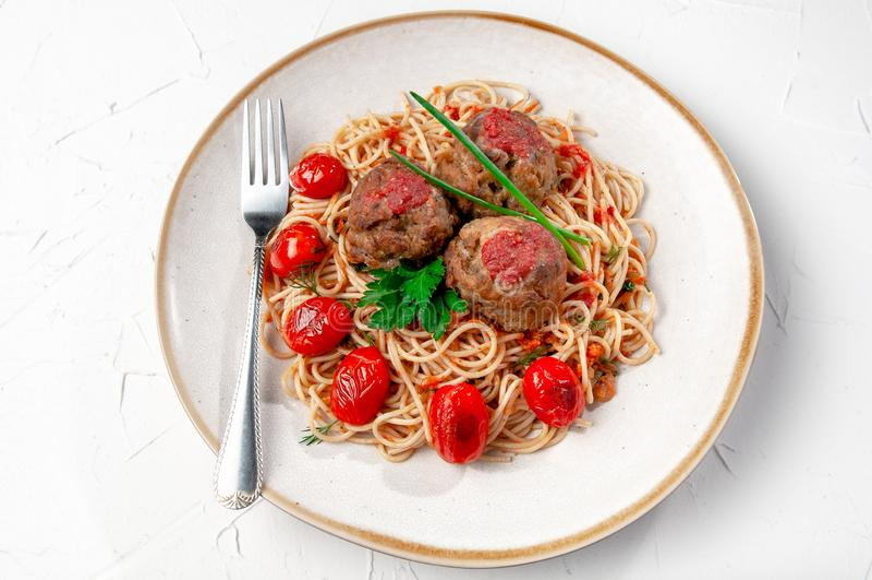tomat f?r meatballspastas?s Dekorerat med gräsplaner och grillade körsbärsröda tomater I den original- plattan med en gaffel Besk arkivbild