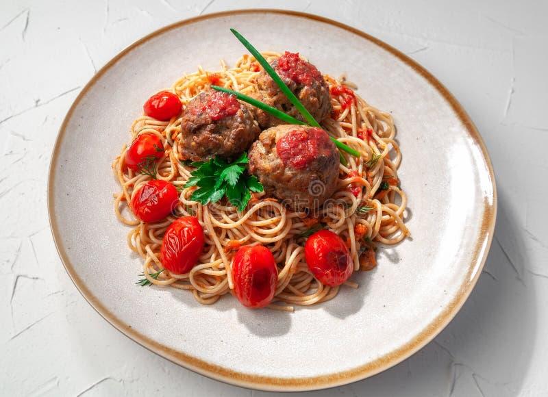 tomat f?r meatballspastas?s Dekorerat med gräsplaner och grillade körsbärsröda tomater I den original- plattan ovanf?r sikt royaltyfria foton