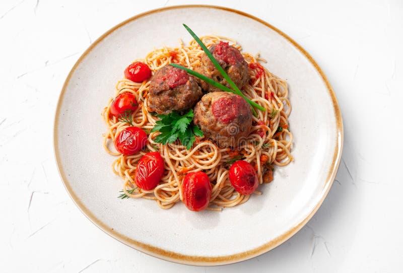 tomat f?r meatballspastas?s Dekorerat med gräsplaner och grillade körsbärsröda tomater I den original- plattan ovanf?r sikt royaltyfria bilder