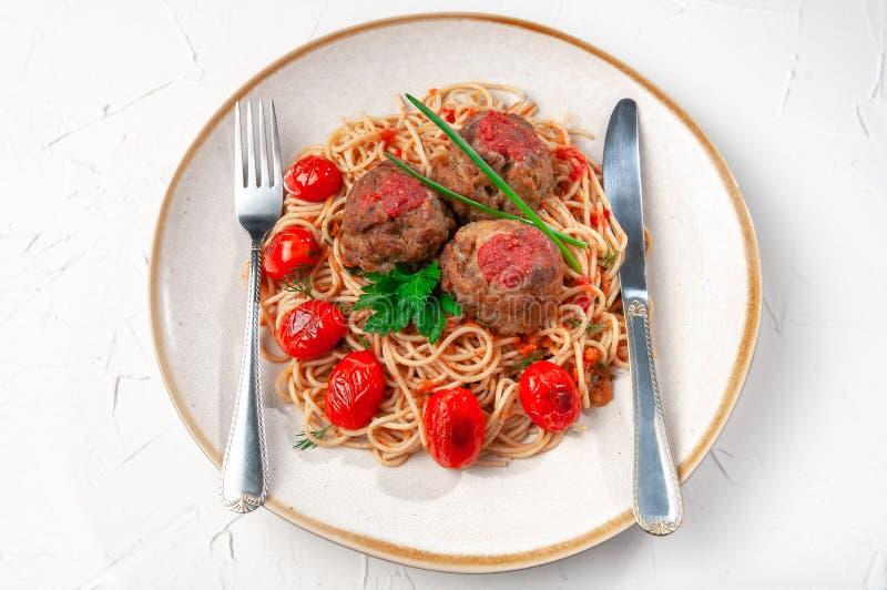 tomat f?r meatballspastas?s Dekorerat med gräsplaner och grillade körsbärsröda tomater I den original- plattan På en plattalögn a royaltyfri foto