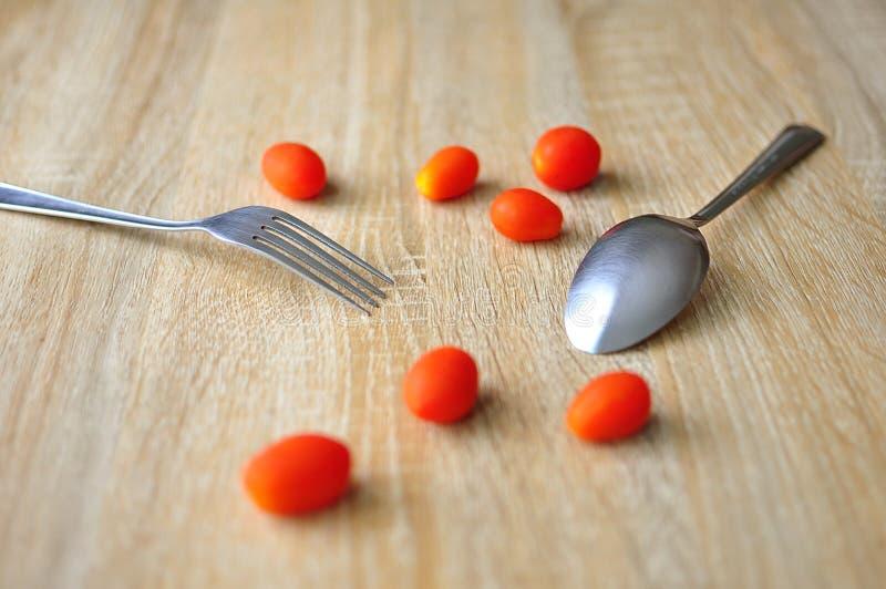 Tomat och gaffel på en träbakgrund fotografering för bildbyråer