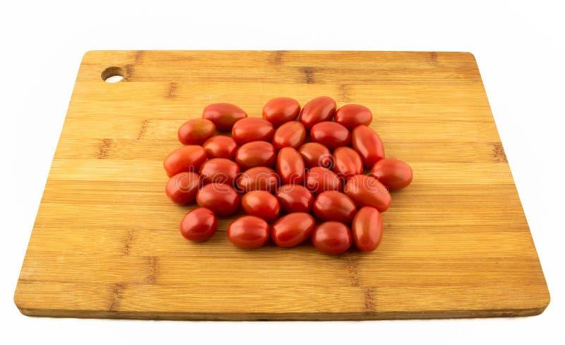 Tomat på träbräde- och vitbakgrund royaltyfri fotografi