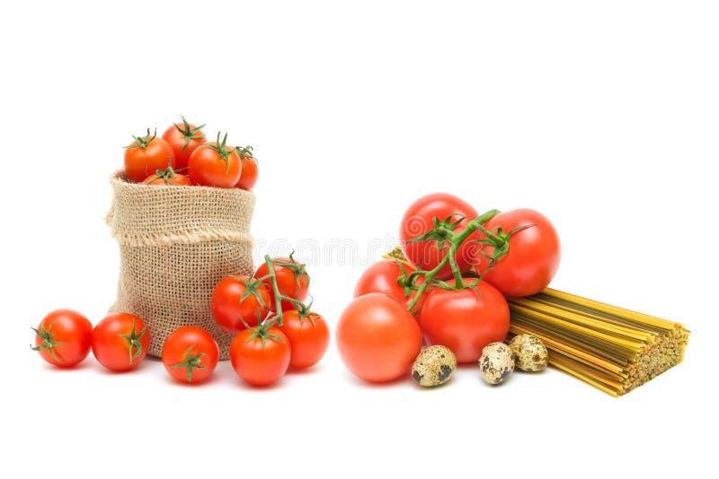 Tomat-, pasta- och vaktelägg på en vit bakgrund arkivbilder