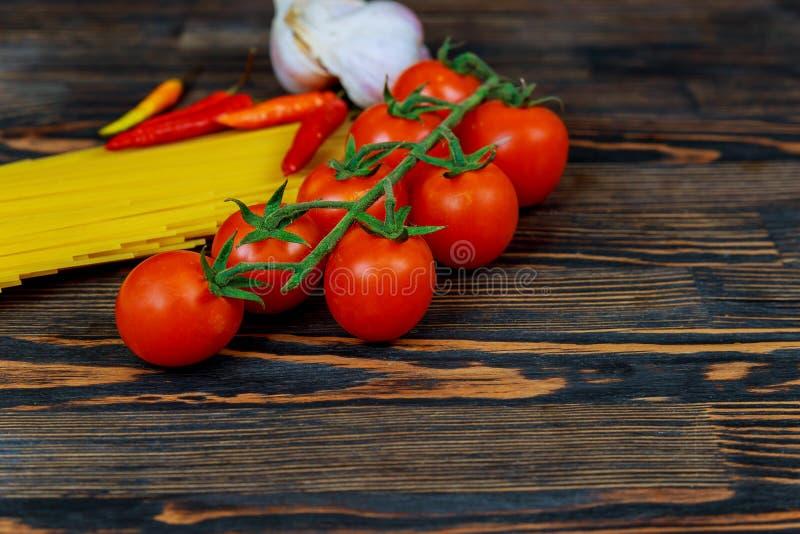 Tomat-, spansk peppar-, vitlök- och pastaingredienser för bästa sikt för förberedelsen av italiensk pasta Ny tomatpepparvitlök oc fotografering för bildbyråer