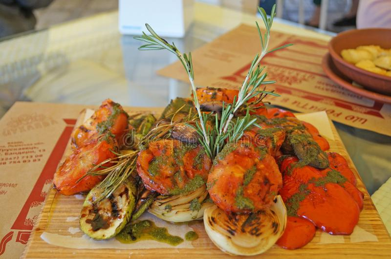 Tomat, zucchini, lökar och aubergine som grillas och dekoreras med rosmarin på en platta fotografering för bildbyråer