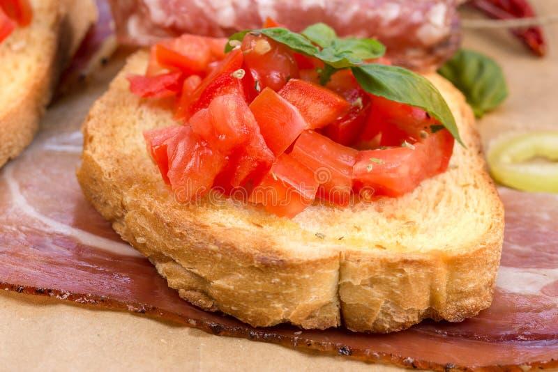 Tomatbruschetti, bruschetta och prosciutto - sund italiensk målmat royaltyfri bild