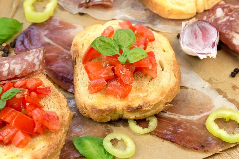 Tomatbruschetti, bruschetta och prosciutto - sunt italienskt mål & x28; food& x29; royaltyfri bild