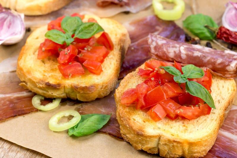 Tomatbruschetti - bruschettaen och prosciuttoen, korv gillar läckert mål fotografering för bildbyråer