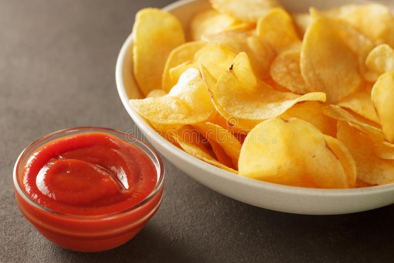 Tomatdoppsås med frasiga potatischiper i bunke royaltyfri foto