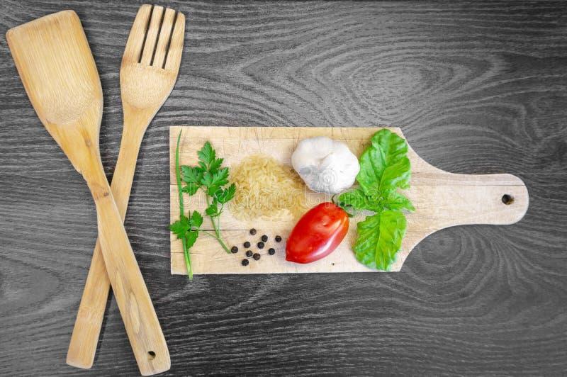 Tomate, albahaca, ajo, perejil, pimienta y arroz frescos con los cubiertos de madera encima de una tabla de cortar con el fondo d foto de archivo
