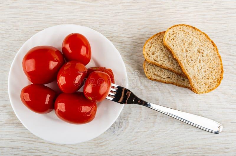 Tomate aufgereiht auf Gabel in der Platte mit marinierten Tomaten, Stücke Brot auf Tabelle Beschneidungspfad eingeschlossen lizenzfreie stockfotografie