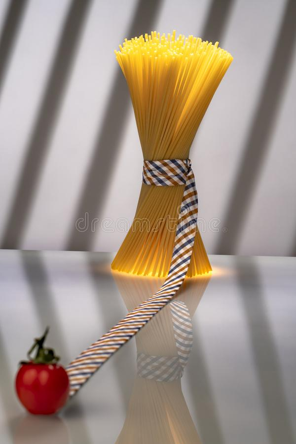 Tomate borroso que lleva sin embargo la cinta al paquete atado de los espaguetis imagen de archivo