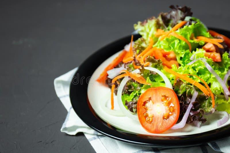 tomate, carotte, oignon, épinards, et laitue de salade sur le conseil noir images stock