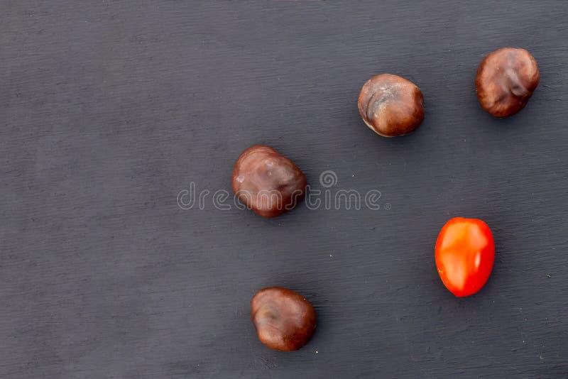 Tomate-cerise rouge lumineuse mûre de châtaigne brune végétale figée de fruit sur la récolte noire d'automne de nourriture de con image stock