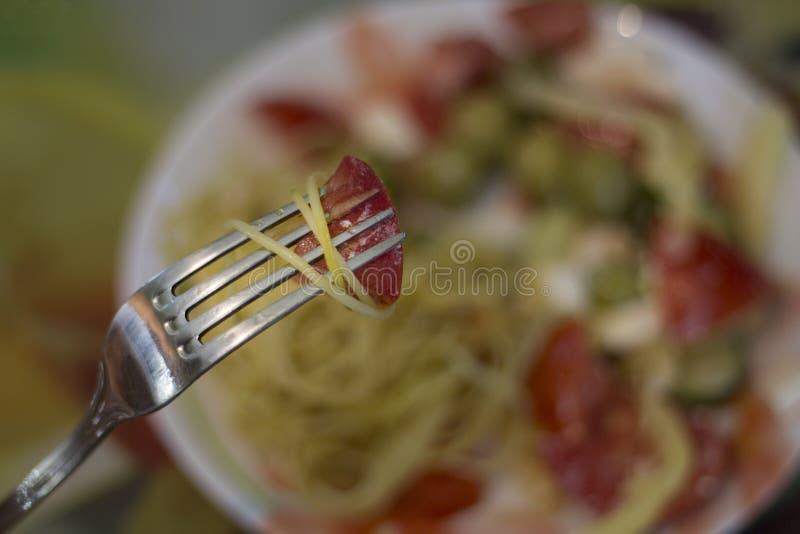 Tomate con espaguetis en la bifurcación y pastas con la ensalada vegetariana imagen de archivo libre de regalías