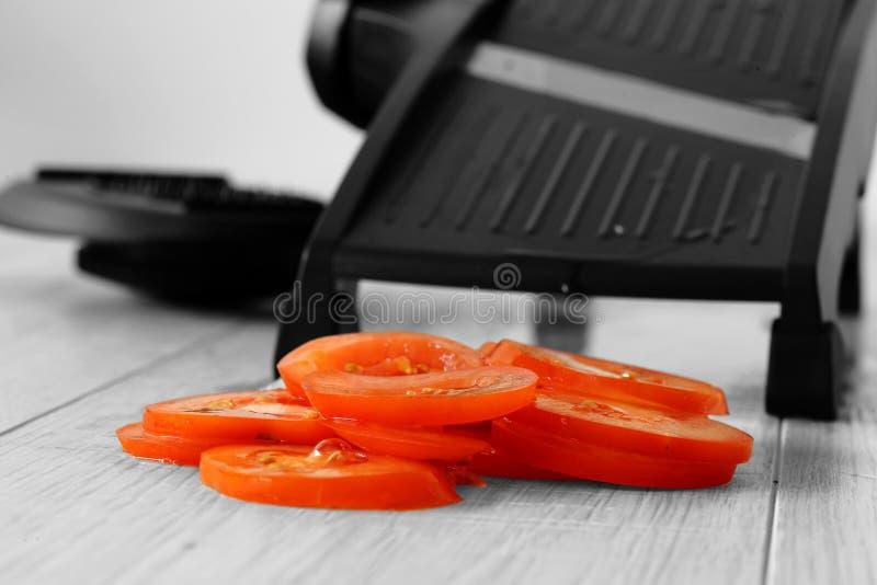 Tomate cortado con mandoline en un worktop de madera gris de la cocina foto de archivo