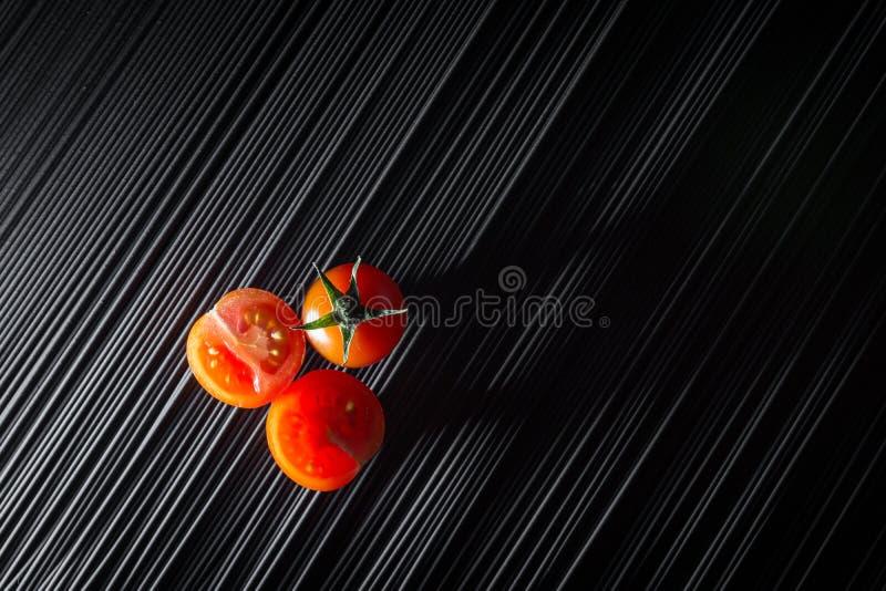 Tomate de cereza y pastas negras crudas fotos de archivo