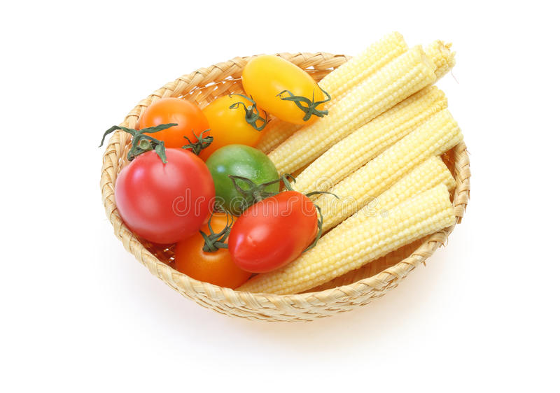 Tomate de la uva y maíz de bebé en una cesta foto de archivo libre de regalías