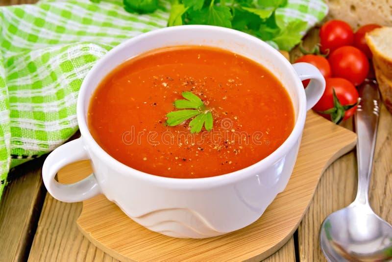 Tomate de soupe dans la cuvette avec la cuillère à bord images libres de droits
