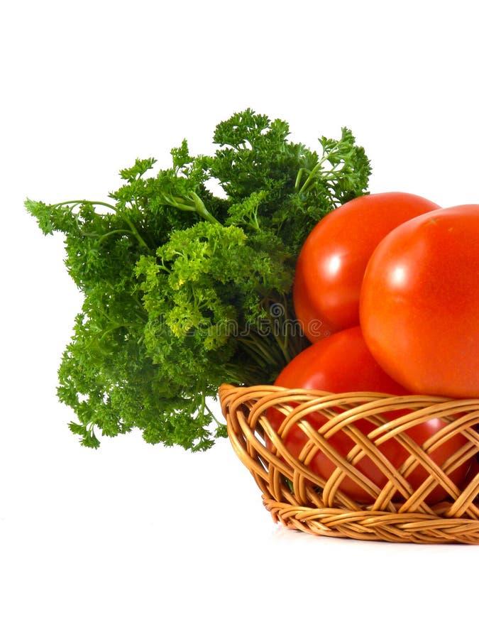 Tomate e salsa na cesta de madeira do ramo isolada no fundo branco imagem de stock