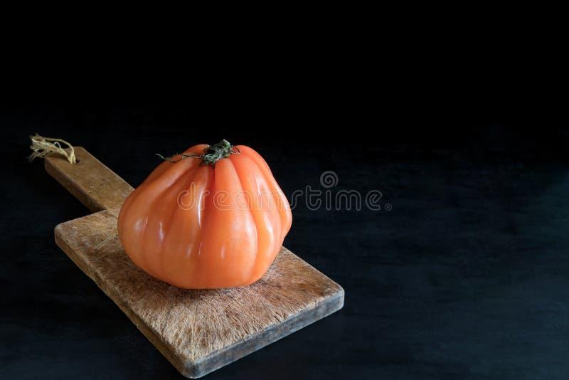 Tomate feio suculento colorido na placa de corte de madeira em um backgound preto, em um estilo rústico e em uma baixa chave foto de stock royalty free