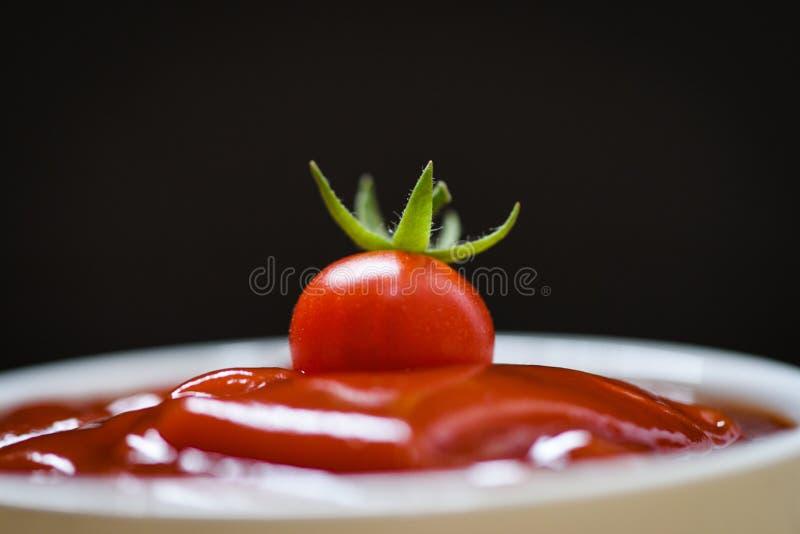Tomate fresco na ketchup e no fundo/fim escuros acima do molho de tomate no copo fotografia de stock