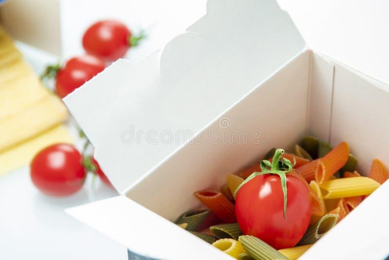 Tomate gelegt in einen Farbteigwarenkasten lizenzfreie stockfotos