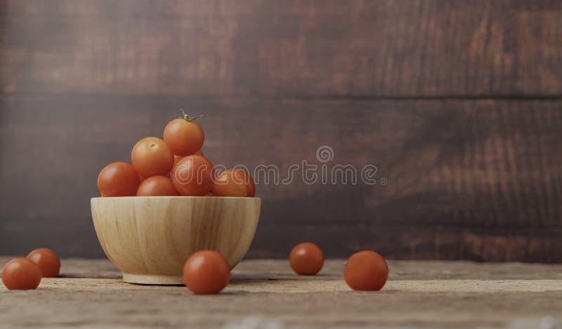 Tomate mûre de groupe dans un endroit en bois de cuvette sur la table en bois photos libres de droits
