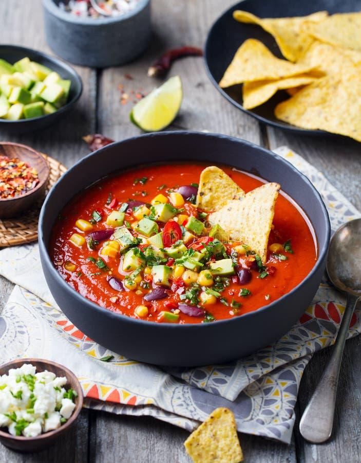 Tomate mexicano, haba, sopa del paprika en cuenco negro con los microprocesadores de los nachos Fondo de madera fotografía de archivo