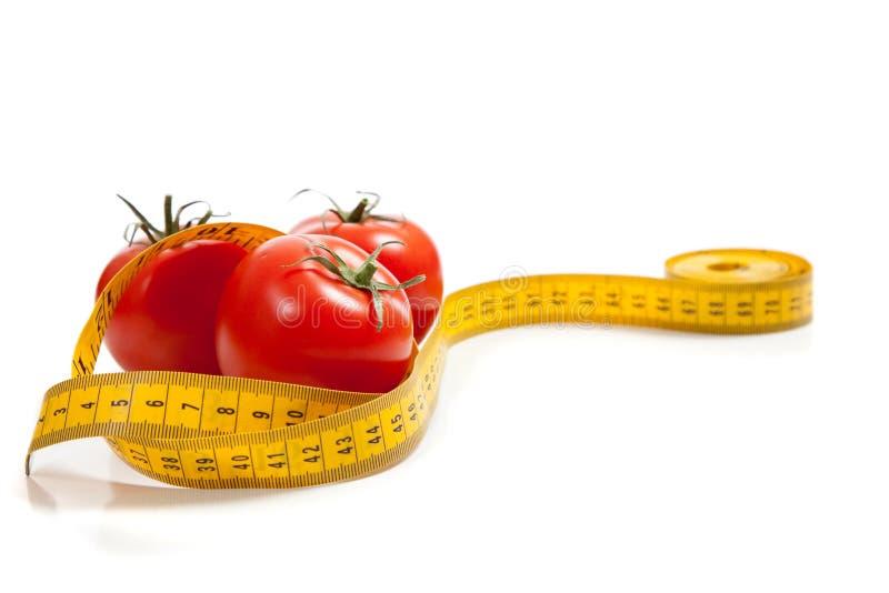 Tomate mit einem Bandmaß lizenzfreies stockfoto