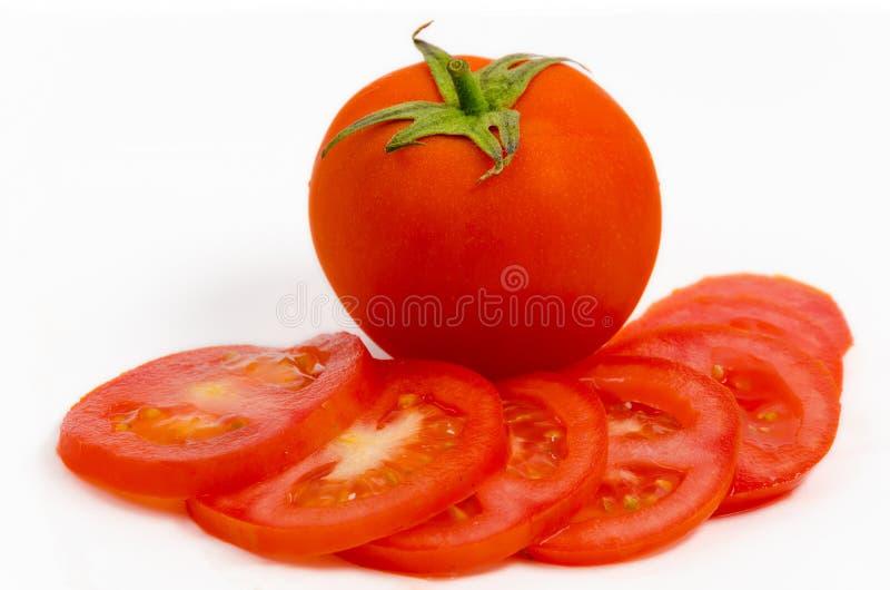Tomate mit Scheiben auf Weiß lizenzfreies stockfoto