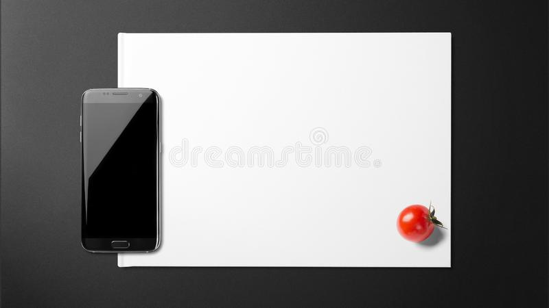 Tomate mit Smartphone auf Papier auf schwarzem Hintergrund lizenzfreies stockfoto