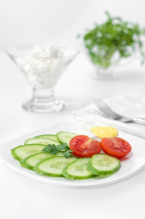 Tomate, pepino e metade cortados de um ovo em uma placa, fundo branco Foco seletivo chave alto foto de stock royalty free