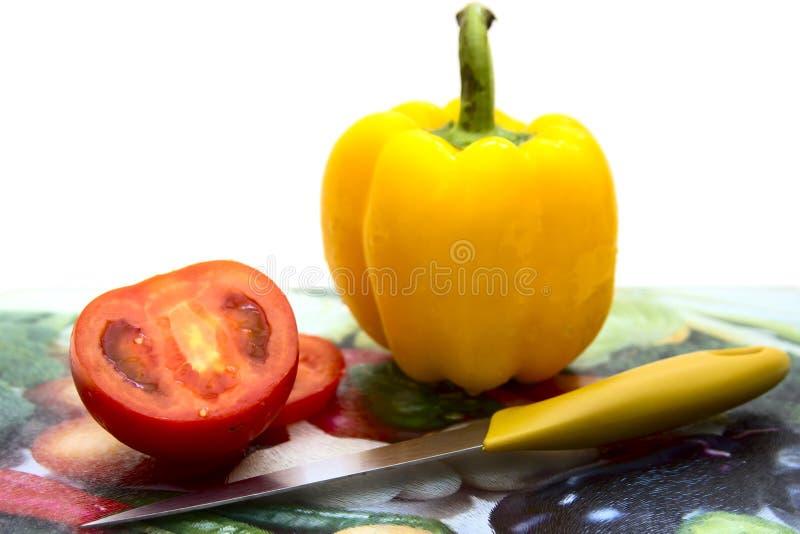 Tomate, pimenta doce em uma placa de corte imagem de stock royalty free