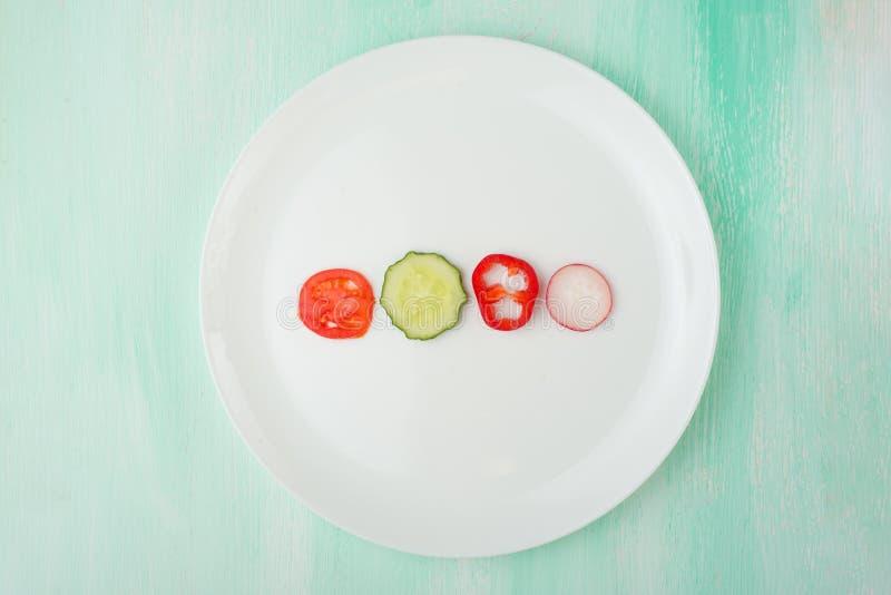 Tomate, pimienta, pepino, y rábanos, creativos de la comida en una placa blanca El concepto de consumición imagenes de archivo