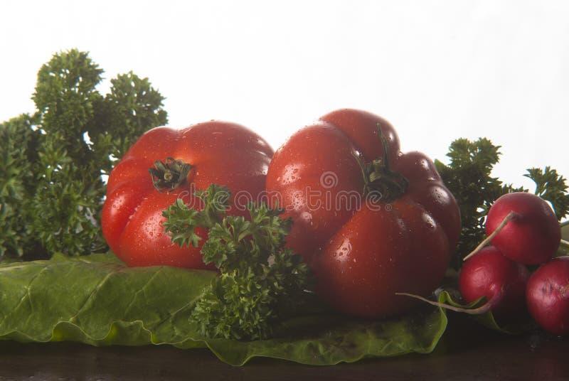 Tomate, Rettich, Mange und Petersilie auf Holzoberfläche stockfotos