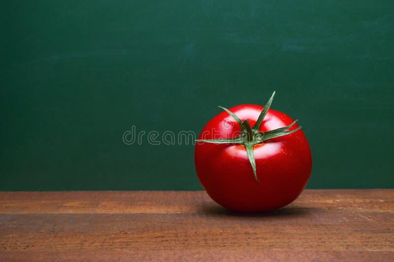 Tomate rojo entero en una tabla de madera Fondo verde Alimento biológico Cocinar los ingredientes Contador de tiempo de Pomodoro imagen de archivo