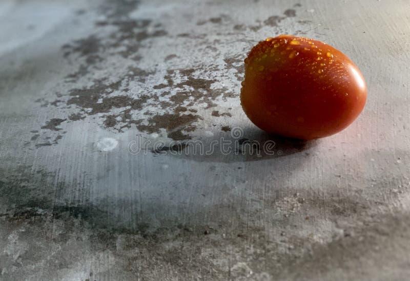 Tomate rouge avec des gouttes de l'eau d'isolement sur le fond rustique, photographie de nourriture photos stock