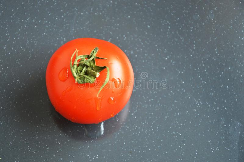 Tomate rouge juteuse sur le fond gris photos stock