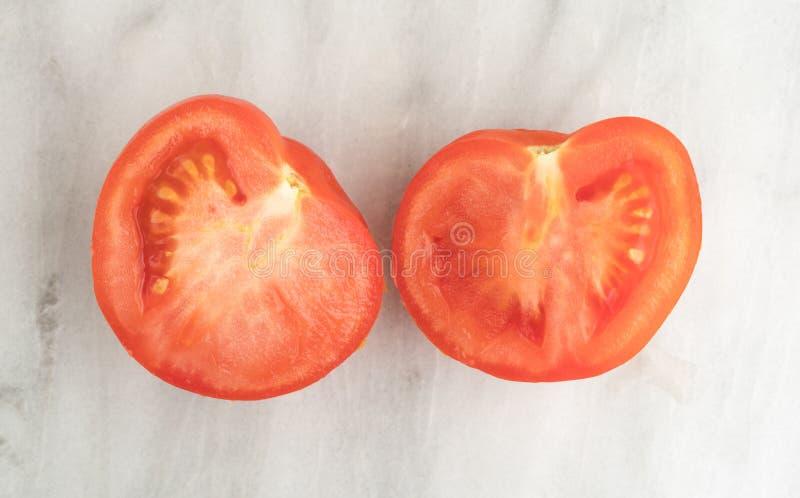 Tomate rouge organique divisée en deux sur une planche à découper de marbre images libres de droits