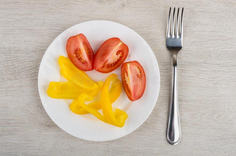 Tomate vermelho e pimenta doce amarela na placa e na forquilha imagem de stock royalty free